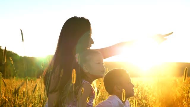 stockvideo's en b-roll-footage met aziatische moeder met kinderen zitten in het veld in de zomer, punt op iets, familieconcept, zijaanzicht - alleenstaande moeder