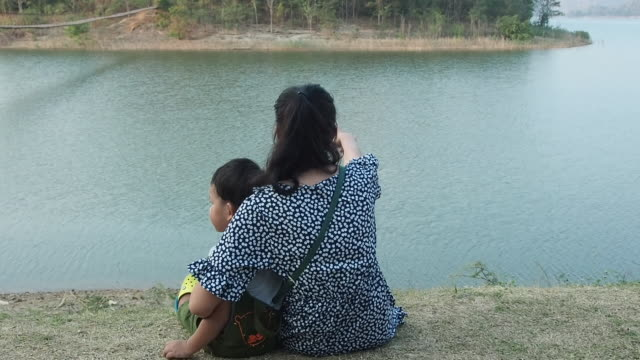 Asian mother with children sitting by the river
