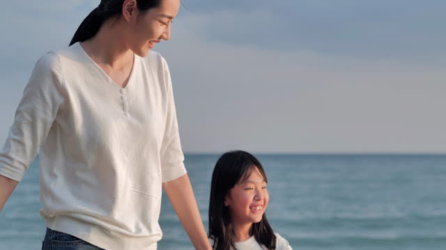 Asian mother with little girl walking with fun along edge of sunset sea surf on sand beach.Happy family holidays.Vacations video