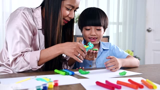 Asian mother work home together with son. Mom and kid play dough. Child creating plasticine clay model. Woman lifestyle and family activity.