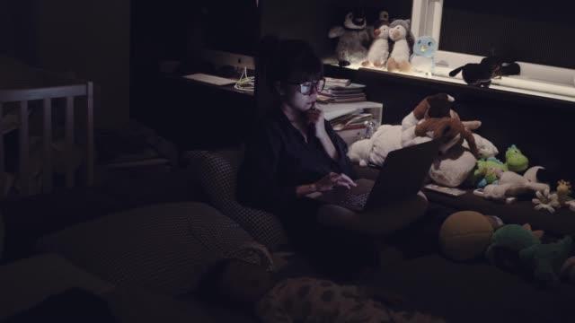 asiatiska mamma arbetar hemma med hennes pojke på natten - working from home bildbanksvideor och videomaterial från bakom kulisserna