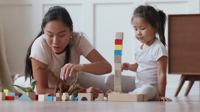 Asian mum playing with daughter building castle of wooden blocks