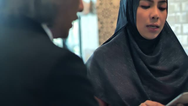 vídeos de stock e filmes b-roll de asian muslim business team meeting at a cafe using tablet. business people meeting partnership.business adviser analyzing financial figures of the company while meeting.business people technology and teamwork concept.arab youth - senior business woman tablet