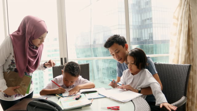 asian muslim family doing homework together - etnia malese video stock e b–roll
