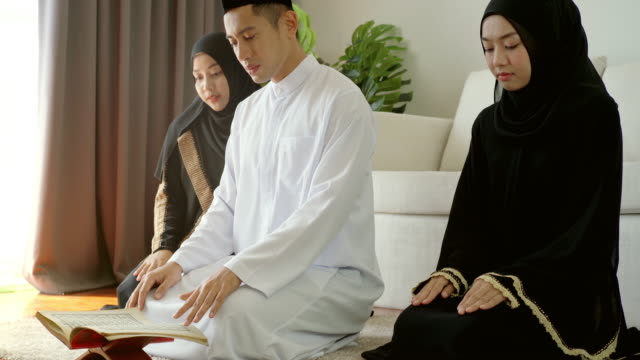 Asian Muslim Family Praying and Prostrating at Home