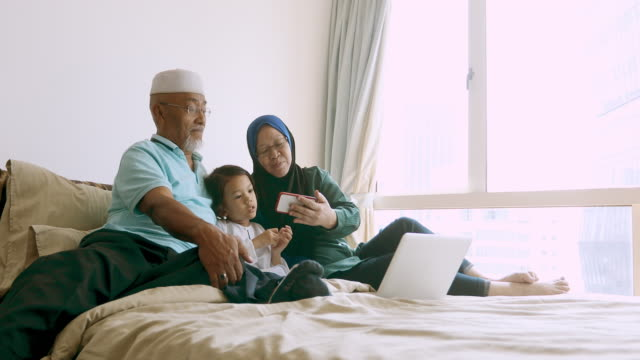 asian muslim grandparents looking at a mobile phone with their granddaughter - etnia malese video stock e b–roll