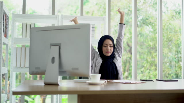 Asian muslim lady stretch her body at the office.