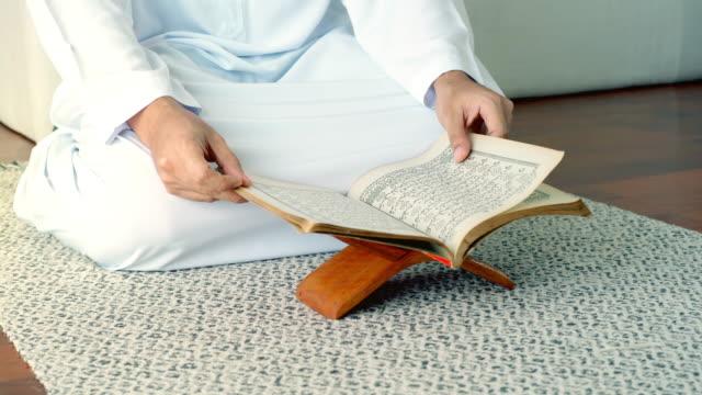 stockvideo's en b-roll-footage met aziatische moslim man bidden en prostrating thuis - koran