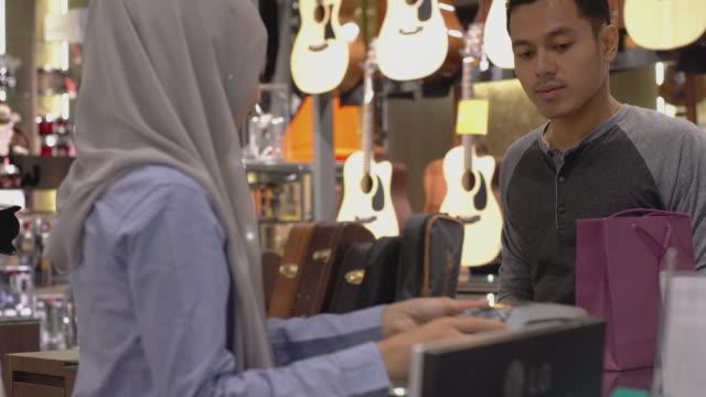 vídeos de stock, filmes e b-roll de homem muçulmano asiático usando pagamento de smartwatch - pin