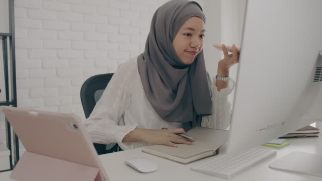 asian muslim woman student or businesswoman waring hijab.working from home with computer and smartphone.concept of social distancing working alone at home in the epidemic situation of covid-19. - didattica a distanza video stock e b–roll