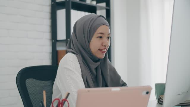 asiatisk muslimsk kvinna student eller affärskvinna stridande hijab. arbeta hemifrån med dator- och mötesvideokonferens online. begreppet socialt avståndstagande arbetar ensam hemma i den epidemiska situationen i covid-19. - hijab bildbanksvideor och videomaterial från bakom kulisserna