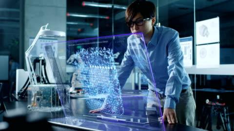 asiatische neuronales netzwerk ingenieur verwendet moderne computer mit transparenten holographische displays. monitor zeigt interaktive künstliche intelligenz schnittstelle. in modernen glas und beton büro erschossen. - hologramm stock-videos und b-roll-filmmaterial