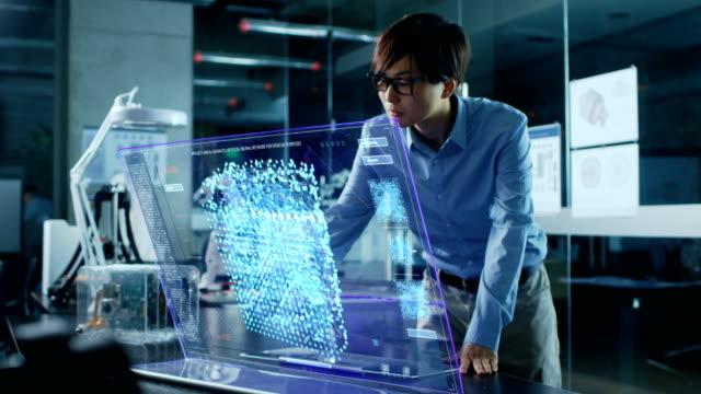 asian neural network engineer uses modern computer with transparent holographic display. monitor shows interactive artificial intelligence interface . shot in modern glass and concrete office. - apprendimento automatico video stock e b–roll