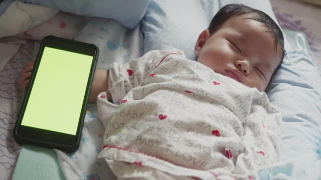 vídeos de stock, filmes e b-roll de bebê recém-nascido asiático dormindo com tela verde smartphone - novo bebê