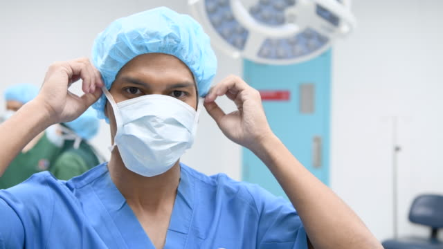 Asian nurse removing surgical mask and smiling