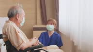 istock Asian nurse taking care of mature male patient sitting on wheelchair in hospital. Young woman and old man wearing surgical face mask for protection of covid 19 pandemic. Girl smile to elderly man. 1280918120