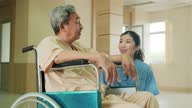 istock Asian nurse taking care of mature male patient sitting on wheelchair in hospital. Young woman talk to old man and look after old patient recovering from surgery operation. Girl smile to elderly man. 1282638800