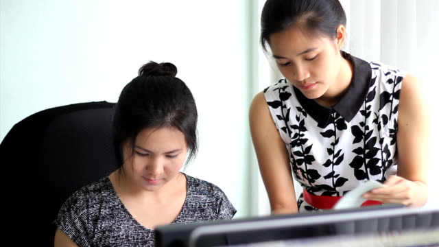 Asian Office Workers Going Over Numbers video