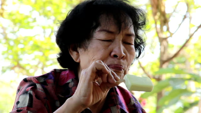 Asian old woman eating ice cream.