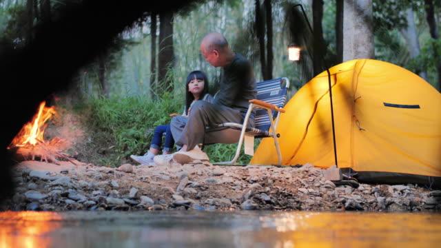 vidéos et rushes de homme et bébé plus âgés asiatiques parlant et appréciant dans le camping près du feu de camp sur la forêt. famille, mode de vie, personnes, multi-génération, personnes âgées, vacances, relation, retraite, soins sains et concept de médecine. un  - camping