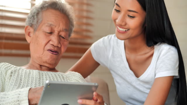 Asian older woman talking to young black female caregiver help patient education on tablet to Covid-19 virus medical at home. Education, Medical, Caretaking, Technology, Senior Care, Retirement, Volunteer, Charity, Nursing home - vídeo