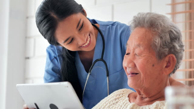 Asian older woman talking to young black female nurse doctor help patient education on tablet to Covid-19 virus medical at home.Education,Medical,Caretaking,Technology,Senior Care,Retirement,Volunteer,Charity,Nursing home,Coronavirus or Covid-19 video