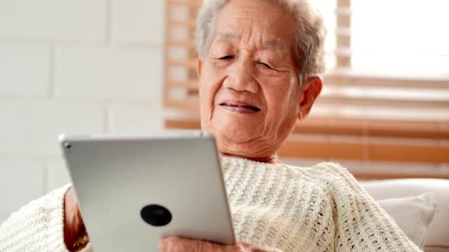 vídeos y material grabado en eventos de stock de mujeres mayores asiáticas paciente teniendo videoconferencia con el médico en la tableta pc en casa. vacaciones para personas mayores, tecnología, personas, jubilación, estilo de vida, global, educación médica, consulta médica, salud y concepto de m - cómodo conceptos