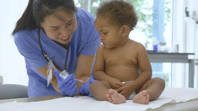 vídeos y material grabado en eventos de stock de pediatra asiático que le da a un bebé una vacuna - vaccine