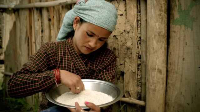 Asian people: A rural woman winnowing rice grain video
