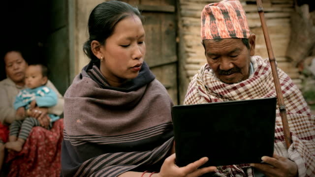 Asian people: A Young woman showing laptop to senior man