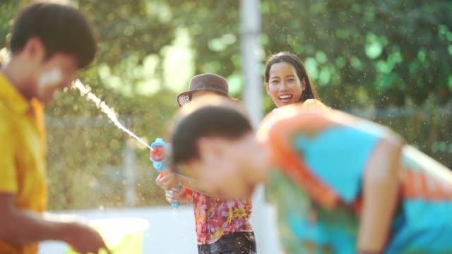 vídeos de stock, filmes e b-roll de os asiáticos estão usando canhões de água tocar festival songkran no verão de abril - ano novo budista