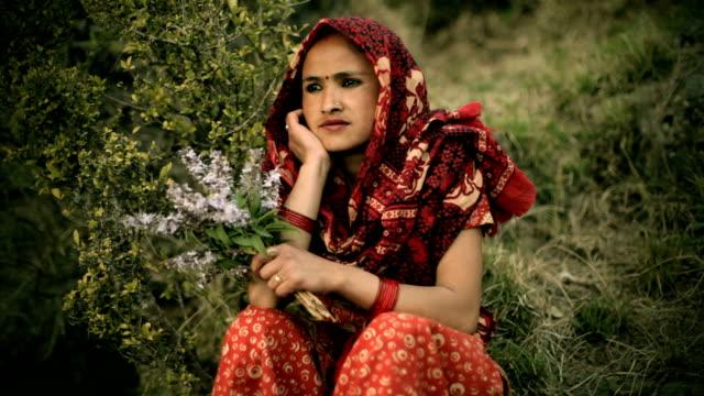 アジア名様:美しい自然の中に座る女性に花。 - ネパール人点の映像素材/bロール