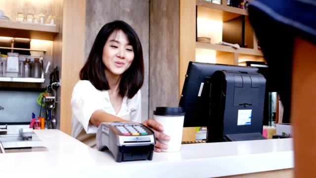 アジア人のためのスマート フォンを使用してコーヒーを購入します。 - 飲食店点の映像素材/bロール