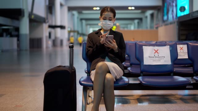 공항 거리에서 마스크를 쓰고 있는 아시아인은 다른 사람들로부터 한 자리에 앉아 covid-19 바이러스로부터 보호해 주시고 있습니다. - 공항 스톡 비디오 및 b-롤 화면