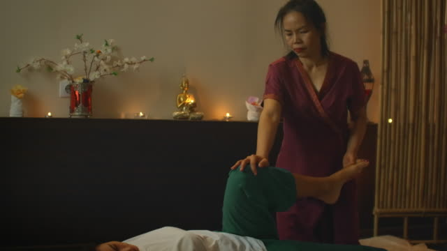asian performs massage in national clothes of thailand. asian spa salon in europe. young caucasian woman relaxes while performing massage - kultura tajska filmów i materiałów b-roll