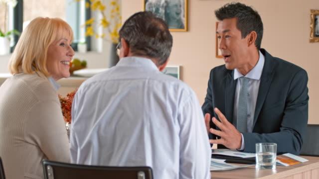 vídeos de stock, filmes e b-roll de banqueiro pessoal asiático, cumprimentando-se com os seus clientes sênior em sua casa - dia do cliente