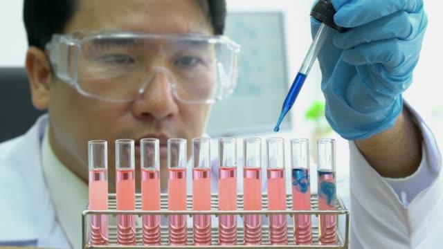 アジアの薬剤師は化学物質の化合物を実験していて、液体を試験管に吸収する。薬学、科学、テスト開発および実験産業の概念。 - 研究所点の映像素材/bロール