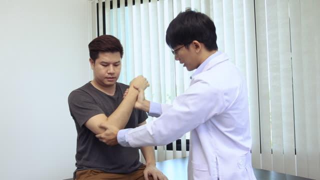 i fisioterapisti asiatici controllano i gomiti dei pazienti che sono stati sottoposti a riabilitazione ortopedica. - fragilità video stock e b–roll