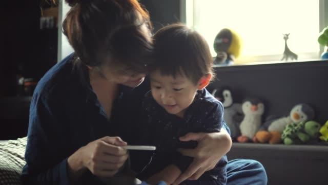 Familia asiática Embarazada hablar y abrazar en la cama en casa. - vídeo
