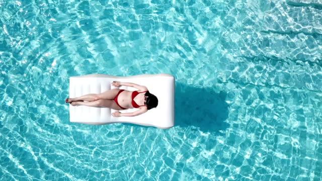 vídeos de stock, filmes e b-roll de mulher asiática grávida em biquini vermelho na vista de topo de inflável flutua na piscina - inflável
