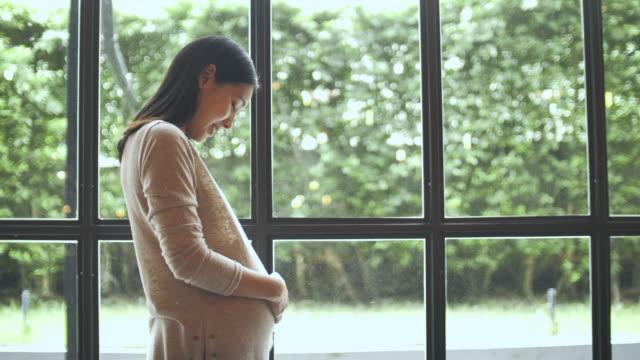 donna incinta asiatica che guarda attraverso la finestra e si strofina la pancia a casa - soft focus video stock e b–roll