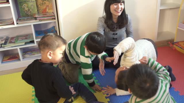 アジア保育園教師レジャーゲームでお子様のスクール形式 - 託児施設点の映像素材/bロール