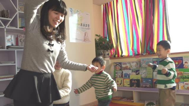 アジア保育園教師レジャーゲームでお子様で、スクール形式、スローモーション。 - 託児施設点の映像素材/bロール