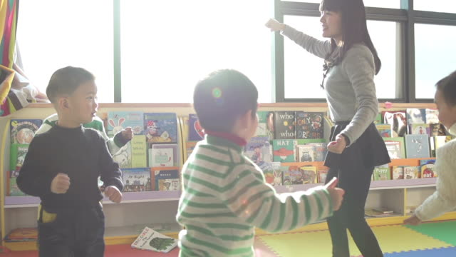 stockvideo's en b-roll-footage met asian preschool teacher play game with children in classroom,slow motion. - chinese etniciteit
