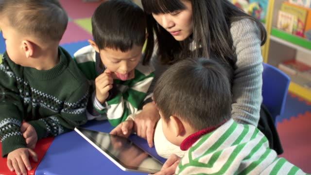 アジア保育園講師によるお子様にデジタルタブレット付き - 託児施設点の映像素材/bロール