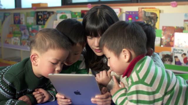 アジア保育園講師によるお子様にデジタルタブレット付き ビデオ