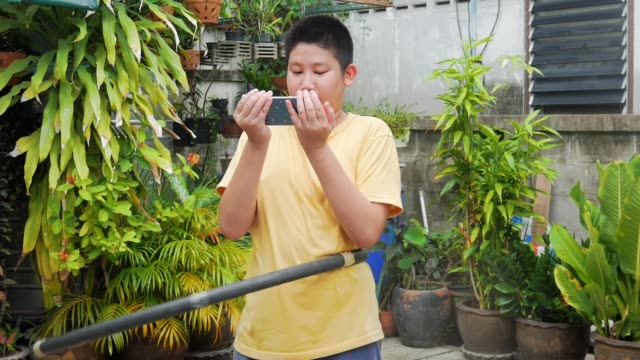 Asian preteen boy playing hula hoop and using smartphone in the backyard at home, lifestyle concept.