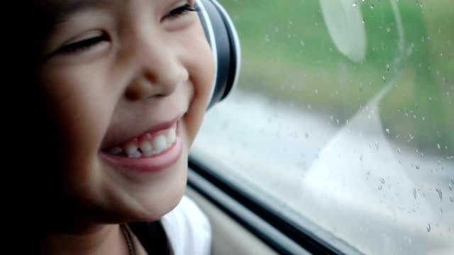 Asian pretty girl listening to music with headphones moving in car and looking away in rainy day Video record with compact camera in light nature. thai ethnicity stock videos & royalty-free footage