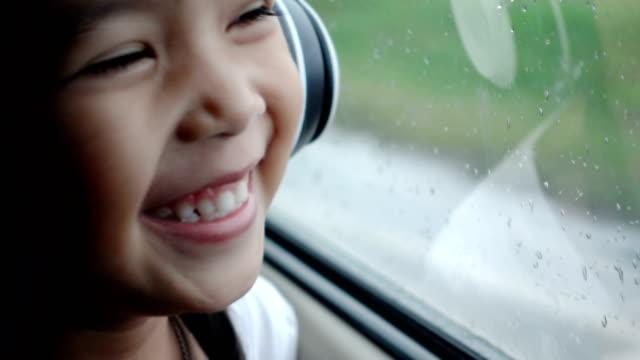 hübsche asiatin musikhören mit kopfhörer im auto bewegt und wegsehen in regnerischen tag - thailändischer abstammung stock-videos und b-roll-filmmaterial