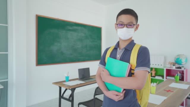 vidéos et rushes de les élèves asiatiques du primaire garçon avec sac à dos et des livres portant des masques pour empêcher l'éclosion de covid 19 dans la salle de classe tandis que de retour à l'école rouvrir leur école, nouveau concept normal pour l'éducatio - enfant masque